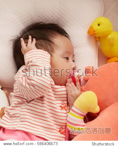 Frontal view of a cute Asian baby girl wake up with a soother in her mouth