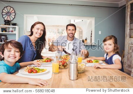 Portrait of happy family with food on dining table at home