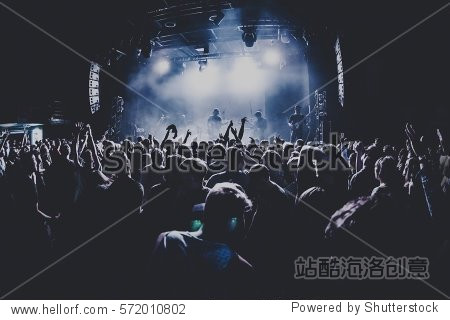 silhouettes of concert crowd in front of bright stage lights. Dark background  smoke  concert  spotlights