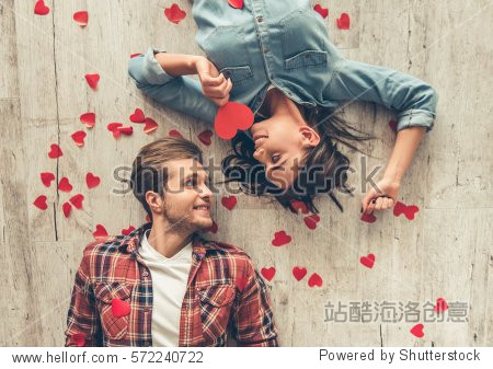 Top view of happy young couple looking at each other and smiling while lying on wooden floor. Girl is holding a red paper heart