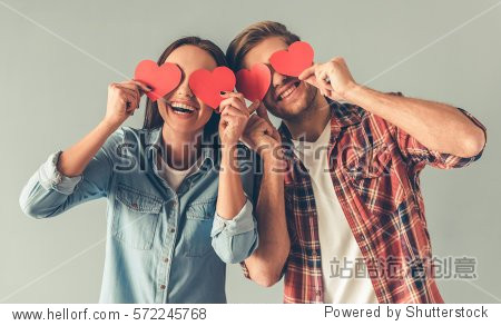 Happy young couple is holding red paper hearts and smiling  on gray background