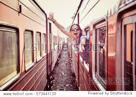 cheerful woman looking out the window of the old train