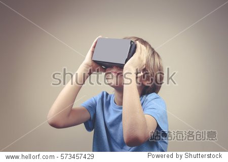 Child using new Virtual Reality, VR cardboard glasses