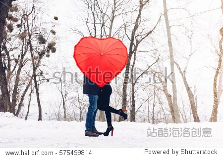 Valentine Day concept. Love in air.Couple in park with heart umbrella