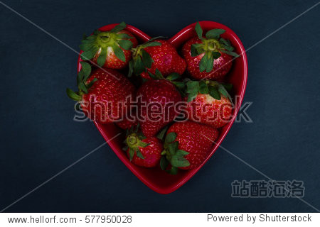 Heart shaped bowl full of ripe strawberries. Flat lay  top view.