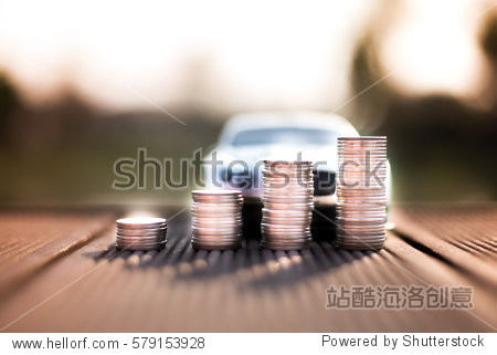 Coins stack with the car model behind  saving for future concept