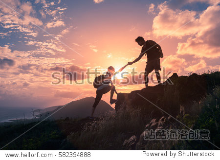 People helping each other hike up a mountain at sunrise.  Giving a helping hand  and active fit lifestyle concept.