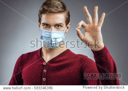Handsome man showing okay gesture. Photo of healthy man wears protective mask against infectious diseases and flu. Health care concept.