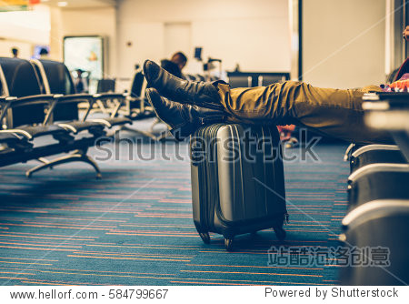 Passenger with carry on luggage waiting for the delay flight in the airport terminal and relaxing.