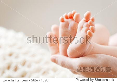 Baby feet in mother hands. Mom and her Child. Happy Family concept. Beautiful conceptual image of Maternity