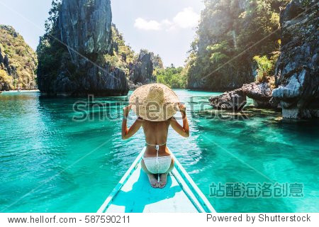 Back view of the young woman in straw hat relaxing on the boat and looking forward into lagoon. Travelling tour in Asia: El Nido  Palawan  Philippines.