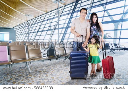 Image of Asian family carrying suitcases for holiday while  standing in the airport terminal