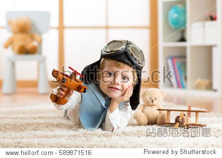 close-up portrait of a little boy playing with a wooden airplane