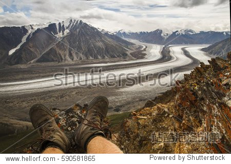 Overseeing a Kaskawulsh Glacier from Observation mountain from perspective of first person. POV. Hiker, hiking shoes, Kluane national park, Yukon, Canada. Global warming. North America. Alaska. Relax.