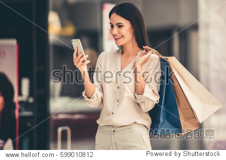 Beautiful girl is holding shopping bags  using a smart phone and smiling while doing shopping in the mall