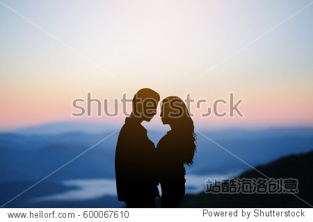 silhouette teenager lovers couple on sunset dusk sky background at the mountain