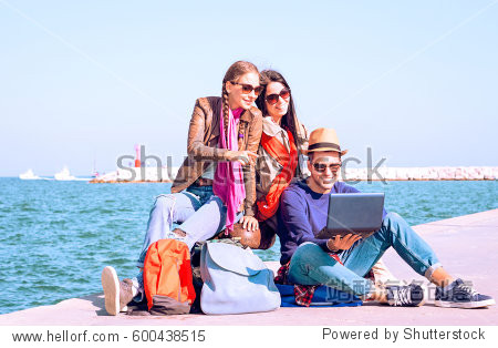Happy best friends traveling on summer holiday are waiting ferry - Cheerful young travelers  using laptop while sitting by ocean at pier on sunny spring break day - Concept of share journey together