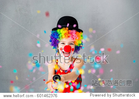 Let's party!! Funny kid clown playing at home. Child shooting party popper confetti. 1 April Fool's day concept