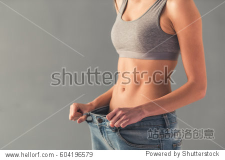 Cropped image of girl pulling her big jeans and showing weight loss