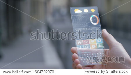 A man in the city  use the transparent phone with the latest technology with holography and watch the weather and the messages. Concept: technology  future and futuristic technology.