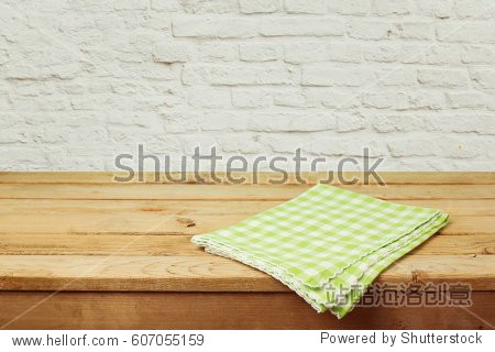 Empty wooden deck table with checked tablecloth over brick wall background for product montage display