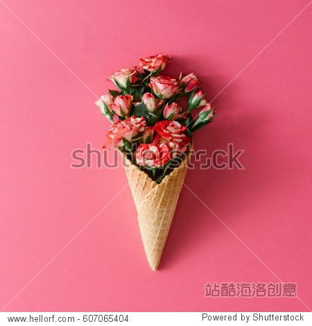 Ice cream cone with colorful flowers on pink background. Flat lay. Minimal summer concept.