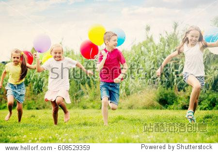 Active kids having fun and running with multicolored balloons at backyard in summer time
