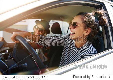 Two fun young women in sunglasses driving in a car in town laughing and smiling as they socialise together  view through open side window