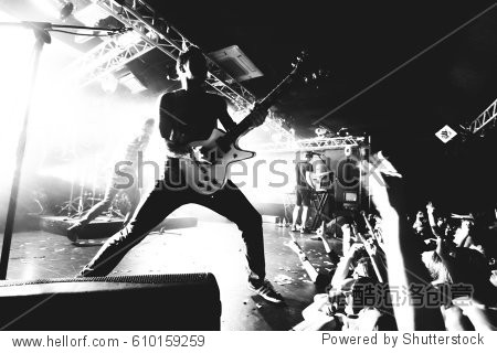 Guitarist on a stage playing rock to the crowd of people. black and white