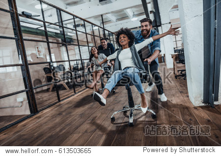 We are the winners!  Four young cheerful business people in smart casual wear having fun while racing on office chairs and smiling
