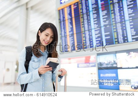 Young woman using cellphone in airport