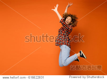 excited curly woman in a checkered shirt and jeans standing over an orange background with empty space for text next to her jumping of happiness
