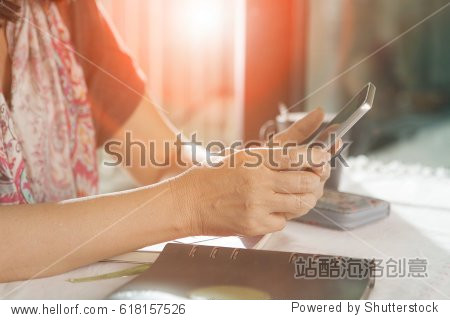 woman hand sitting on working table and using smartphone  for people modern lifestyle theme