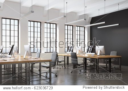 Side view of an open space office with a black wall  many tables with computers on them and a concrete floor. 3d rendering.