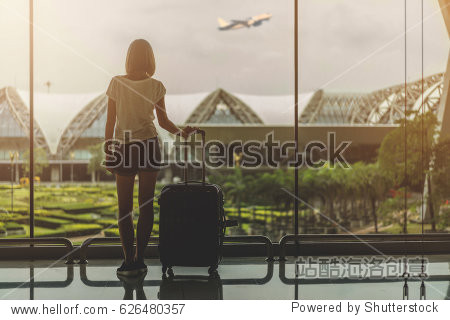 Silhouette of the young female tourist with a bag standing near the window at the airport and looking at the garden outside while waiting for check in. Mock up  copy space for your text.