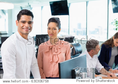 Portrait of smiling business colleagues standing together at desk in office