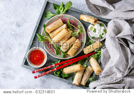 Fried spring rolls with red and white sauces  served in china plate on wood tray with fresh green salad and wooden chopsticks over gray blue texture background. Flat lay  space. Asian food