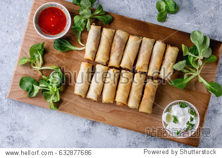 Fried spring rolls with red and white sauces  served on wood serving board with fresh green salad and wooden chopsticks over gray blue texture background. Flat lay  space. Asian food