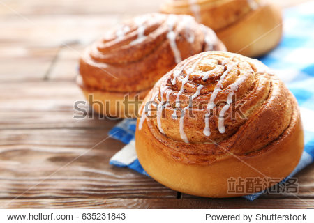 Cinnamon buns with napkin on wooden table