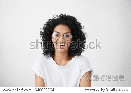 Close up isolated studio shot of good looking cheerful positive young mixed race female with brunette curly hair  smiling broadly  showing her white teeth at camera while having fun indoors