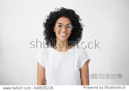 Youth  lifestyle and education concept. Indoor shot of pretty student girl with cute broad smile looking at camera while having rest at home  wearing trendy eyeglasses and white casual t-shirt