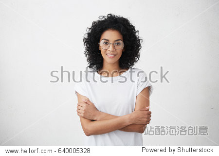 Body language. Isolated studio portrait of constrained young dark-skinned woman in round eyewear standing at white wall with arms folded  looking with subtle smile while visiting her therapist