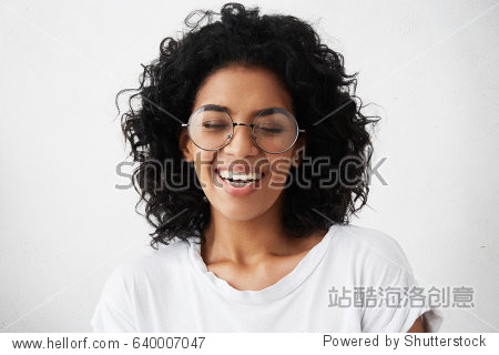 Pretty girl with dark clean skin and beautiful toothy smile laughing out loud at funny joke while having fun indoors with friends  closing eyes in joy  looking carefree and relaxed. Horizontal