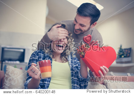 Boyfriend keeps eyes closed to his girlfriend. Young couple enjoying together at home.