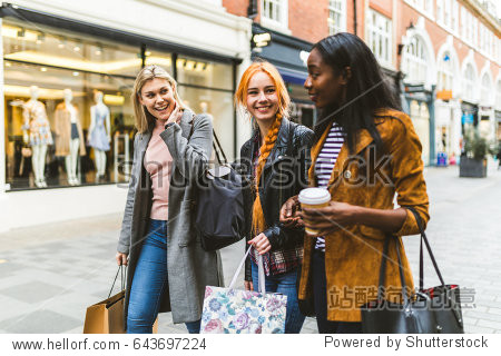 Girls shopping and walking in London. Three girls  multiracial group  having fun in the city while shopping. Best friends sharing happiness  lifestyle and friendship concepts