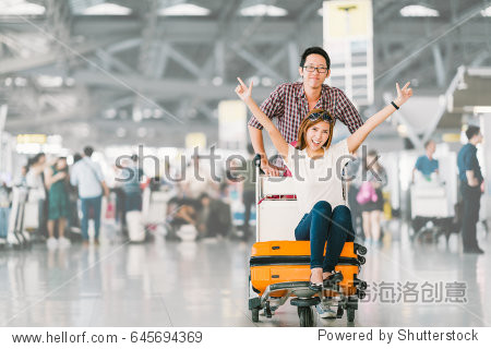 Young Asian tourist couple happy and excited together for the trip  girlfriend sitting and cheering on baggage trolley or luggage cart. Holiday vacation traveling abroad concept  with copy space