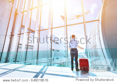 Businessman at airport terminal boarding gate looking at airplane flying through the window
