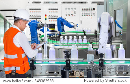 Engineer checking automated robotics in drinks production plant of factory