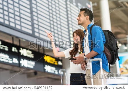 Asian couple traveler holding the smart mobile phone and pointing at the flight information screen in modern an airport  travel and transportation with technology concept.