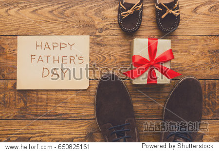 Happy Fathers Day card background on rustic wood with male and child shoes  copy space